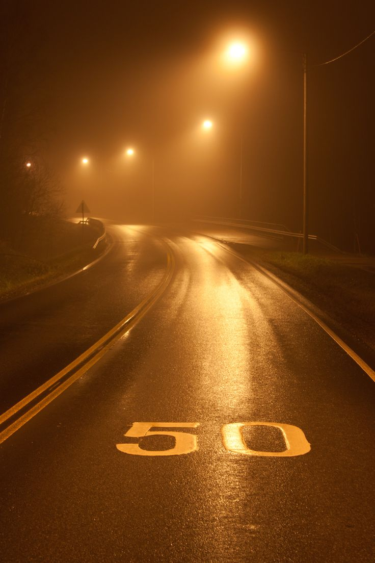 Wet road at night illuminated by glloomy street lights