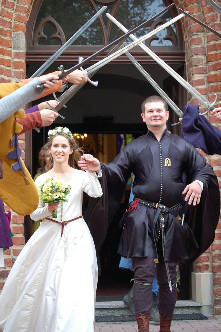 Groomsmen and fathers with swords for bride and groom to walk under after medieval wedding
