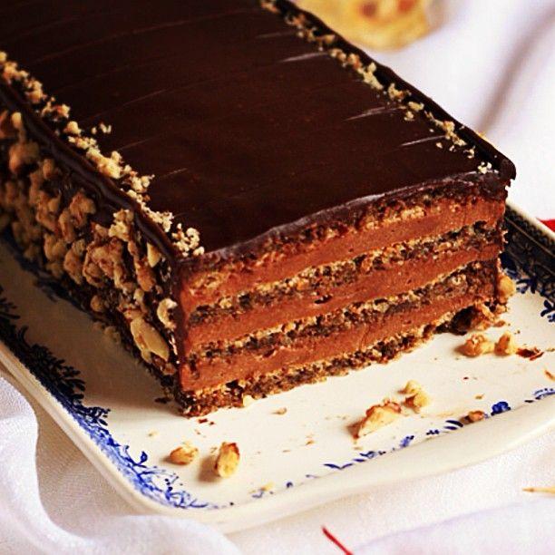 En tårta för chokladälskare! Mäktig chokladbomb med fyra lager valnötsmaräng varvad med len, fluffig chokladkräm och som om det inte räckte, toppad med glansig chokladglasyr.