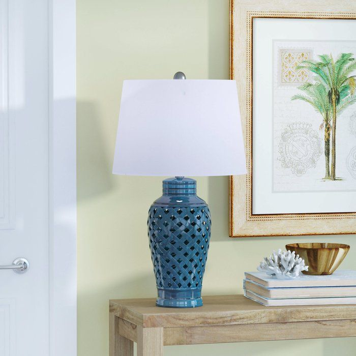 Graceful as it glows, this timeless table lamp instantly ups the island-inspired allure in any abode. Set it atop a weathered wood end table for a little sofa-side illumination as you lounge in the living room, the play up its tropical charm by rolling out a knotted jute rug on the floor below and dotting your seating space with vibrant floral-patterned pillows. Taking on a traditional urn silhouette, its base is crafted of ceramic with pierced details and a glossy solid-hued finish. To…