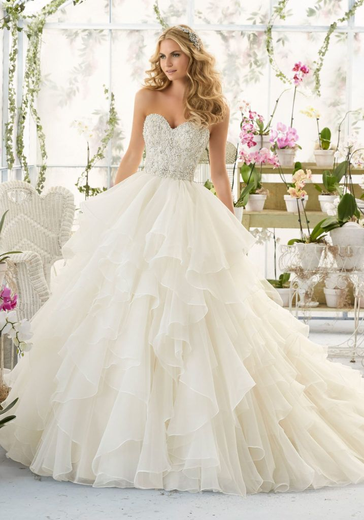 Wedding Dress with Intricate Crystal Beaded and Embroidered Bodice onto a Flounced Organza Skirt. Removable Beaded Satin Belt included. Colors:White/Silver and more