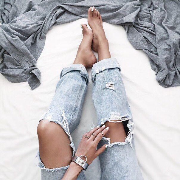 Серый плед + браслет + рваные джинсы + ноги + одеяло + белая простынь + кровать + мода + женская мода + стиль