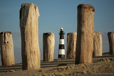Golfbrekerpalen op het strand van Breskens met daartussen de vuurtoren van Breskens.
