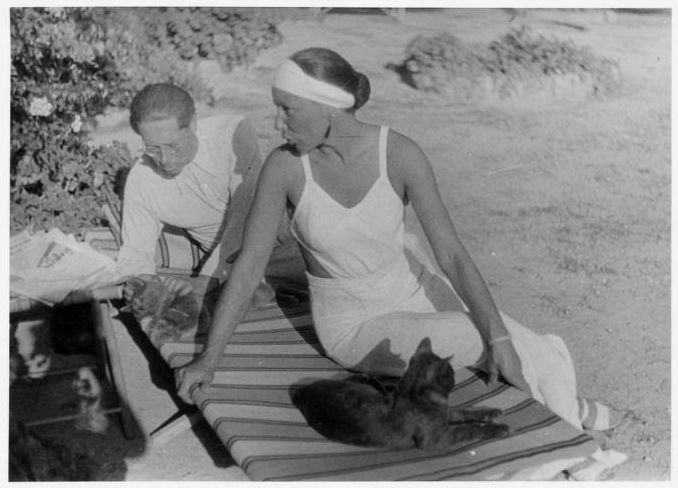 Lion Feuchtwanger Papers, 1884-1958 - Lion Feuchtwanger and wife Marta on the lawn in Sanary, France, 1933-1940. Marta lounges sits on the edge of a longue chair talking to Lion who is sitting next to her. Lion sits listening to Marta petting a cat while another cat sits at the end of the lounger next to Marta.
