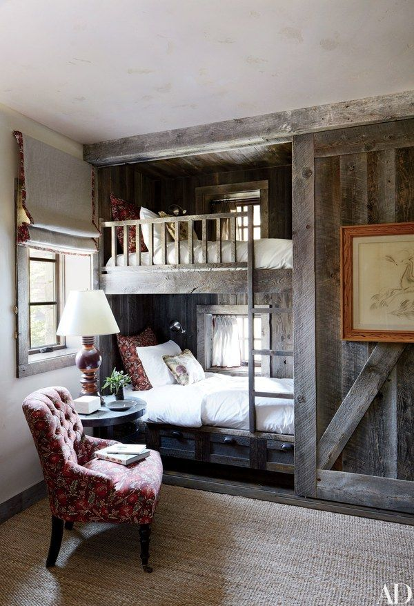 The bunk room in a Montana home decorated by Markham Roberts is partially sheathed in reclaimed corral boards | archdigest.com