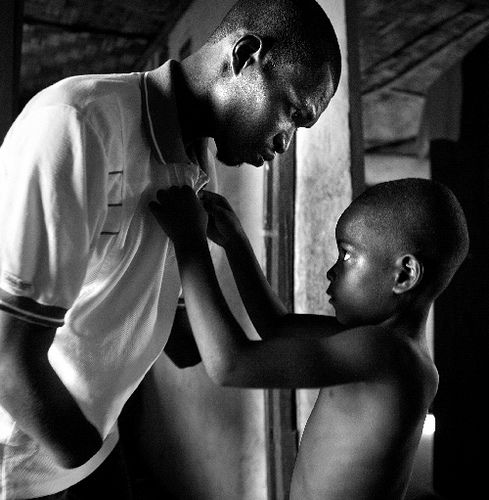 """Abu Bakarr Kargbo, 31, was one of the thousands of amputees afflicted by the Revolutionary United Front (RUF) atrocities during the civil war that devastated Sierra Leone from 1991 till 2002. Both his forearms were cut off.  Young Abu,7, buttons his father's collar in the family's shelter in the camp for amputees, northwest of Freetown."" Yannis Kontos. Polaris. Sierra Leone. 2005."