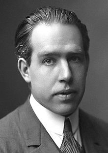 Niels Bohr (7 October 1885– 18 November 1962) was a Danish physicist who made foundational contributions to understanding atomic structure and quantum mechanics, for which he received the Nobel Prize in Physics in 1922. He developed the model of the atom with the nucleus at the center and electrons in orbit around it, which he compared to the planets orbiting the sun.