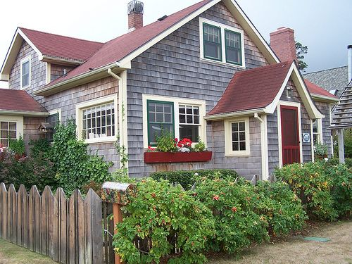 Beach cottage. Natural weathered shingles, pale yellow trim, dark red window boxes and door.