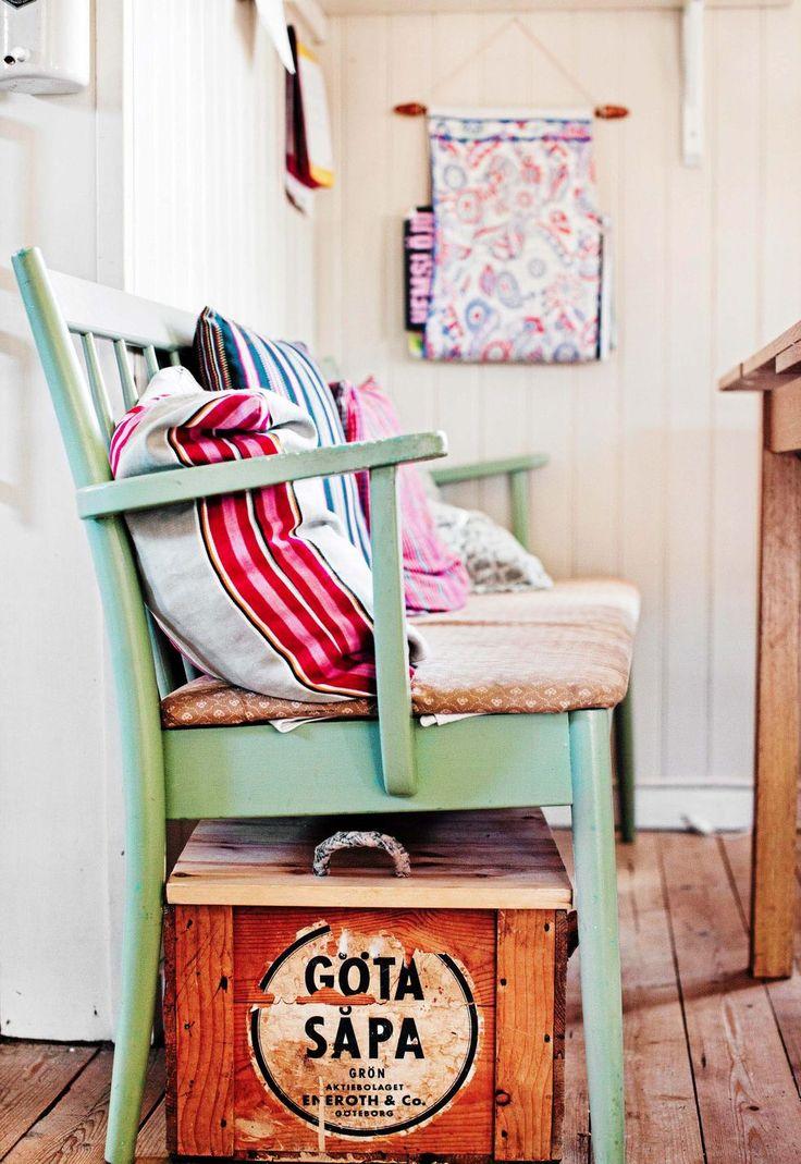 """Soffa köpt på second hand och målad med linoljefärg. I lådan """"Göta såpa"""" har familjen pappersinsamling. Kuddar sydda av loppistyger."""