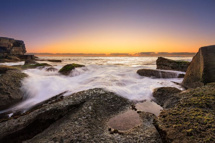 Rich colour of pre-dawn, with gentle waves crashing on the rocks at Kamay Botany Bay National Parl, NSW Australia