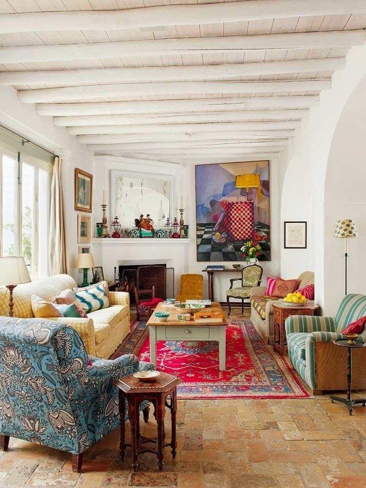 salon de style hippie chic avec kilim en rouge et bleu, tableaux accrochés aux murs et poutres au plafond