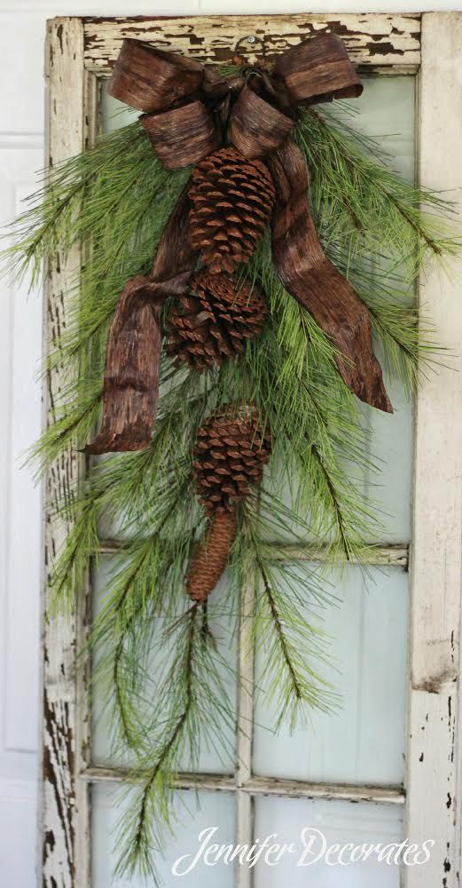 Realistic and rustic door swag adorned with pinecones and a stunning woods…