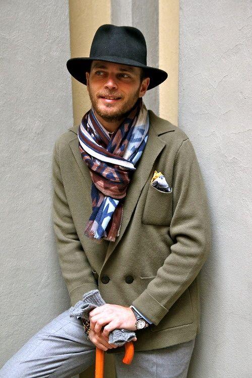 Comprar ropa de este look:  https://lookastic.es/moda-hombre/looks/blazer-cruzado-pantalon-de-vestir-sombrero-panuelo-de-bolsillo-bufanda-guantes/2217  — Sombrero Negro  — Blazer Cruzado de Lana Verde Oliva  — Pañuelo de Bolsillo Blanco  — Bufanda Multicolor  — Guantes de Lana Grises  — Pantalón de Vestir Gris