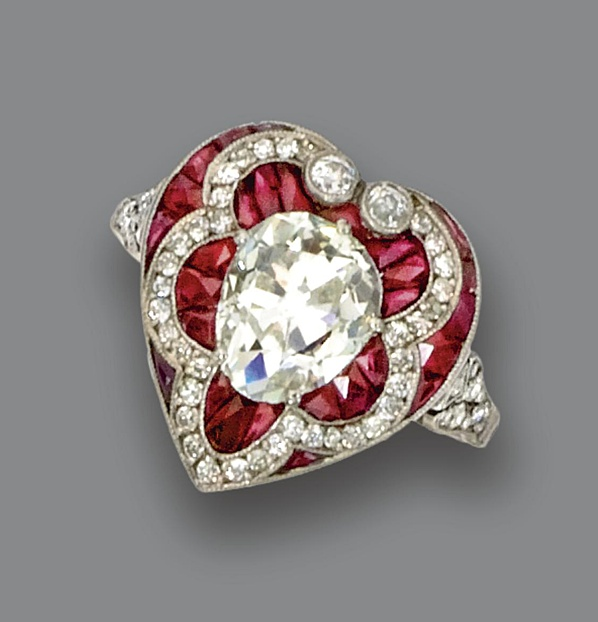 DIAMOND AND RUBY 'HEART' RING. The modified pear-shaped diamond weighing approximately 1.35 carats within a heart-shaped panel set with small old European-cut diamonds and French calibré-cut rubies, mounted in platinum, size 6½.