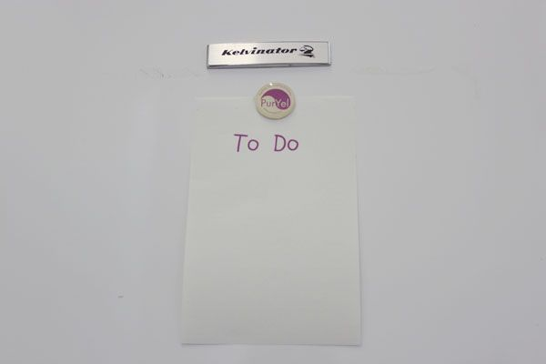 To Do list stuck on fridge with domed magnet