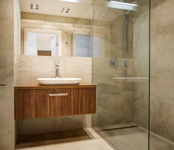 Prysznic w łazience z odpływem liniowym i szklaną ścianą oddzielającą prysznic od reszty pomieszczenia.