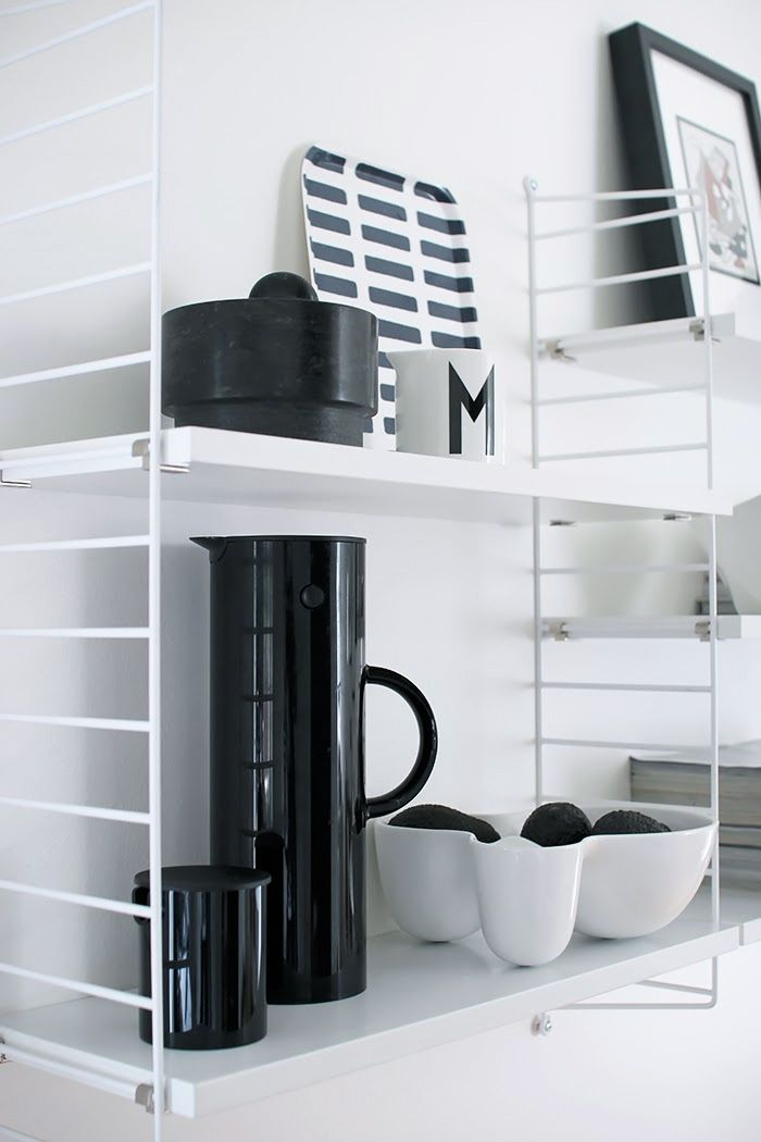 White String shelf with a black vacuum jug and a creamer by Stelton via Nordic Days.
