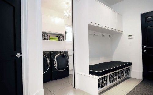 Black  white mudroom with a laundry center tucked behind it