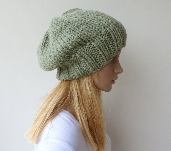 Hand knitted in a double strand of dusty green wool alpaca blend yarn this beautiful slouchy beanie will become a favourite. It is smooth, soft and warm with alpacas incredible insulating qualities. Because I have knitted using a double strand it is a chunky knit hat that is a delight to wear.  * easily stretches for most adult and teen head sizes 21-23 (53.5- 59cm) * Soft , warm and smooth for easy wear in 70% wool and 30% alpaca * Measures 10(26cm) from base of ribbing to top of hat  The…