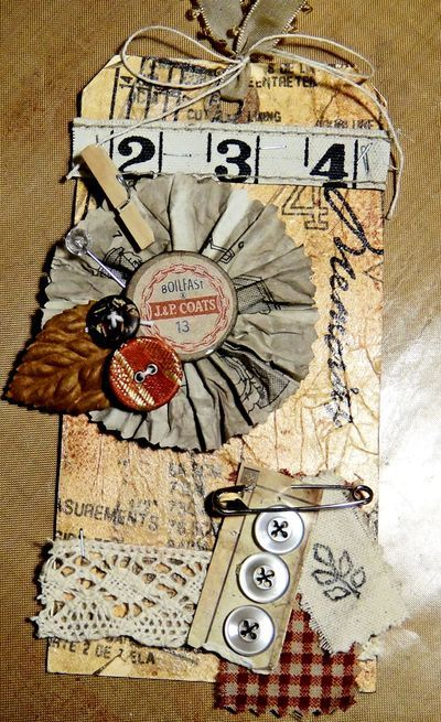 Nancy Burke uses a sewing pattern for the background of this Sewing-themed tag.  Love the buttons and swatches of fabric