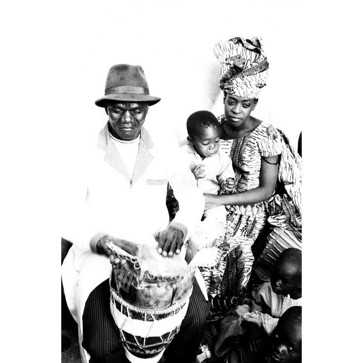 """#Djembe Sound. Opera dell'archivio dell'agenzia """"D.F.P"""", fondata da Dani Maria Turriccia nel 1963. La fotografia appartiene a un reportage, condotto in Nigeria nel 1975.E' un giorno di festa in un piccolo villaggio nigeriano, in primo piano un quadretto familiare: il padre suona il tradizionale djembe, mentre la madre in abiti tradizionali cura amorevolmente il loro piccolo erede."""
