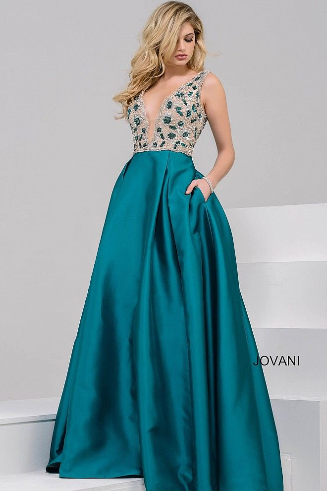Gorgeous floor length a-line teal prom ballgown with pockets features sleeveless green and silver crystal embellished bodice over nude underlay with plunging neckline and v back.