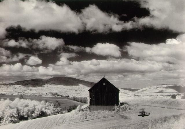 Minor White, 'Barn and Clouds', in the vicinity of Naples and Danseville, New York, 1955. The photographs were taken using large format infrared film, typified by their darkened skies and glowing grass and leaves