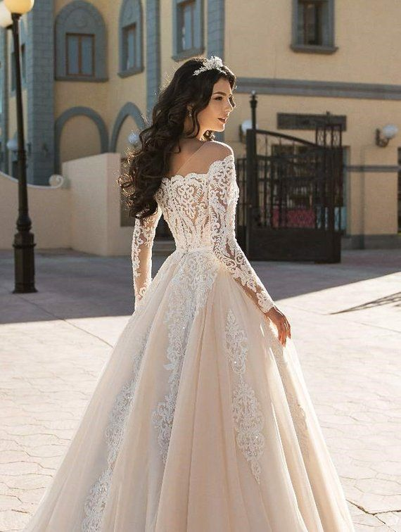 Lace wedding dress with corset an off-shoulder and long lace sleeves, transparent back with buttons, light beige tulle skirt with lace