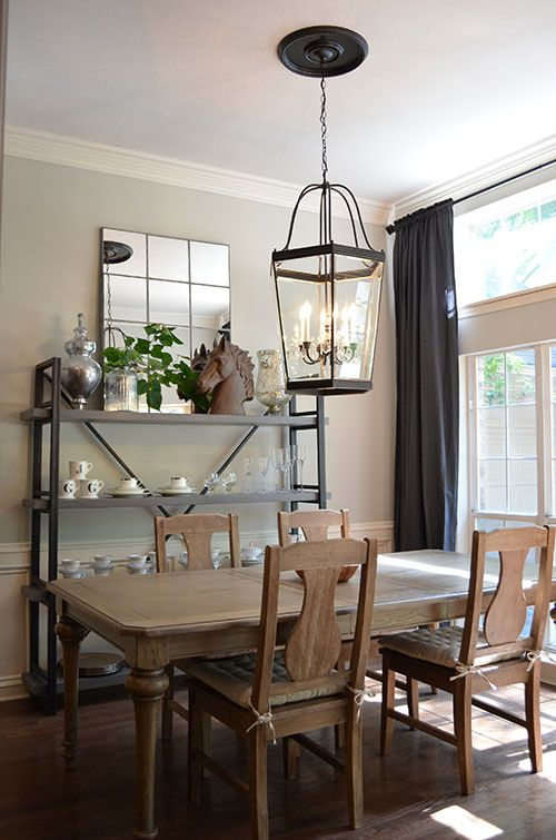 Serene grey dining room with thrift store lantern chandelier (spray painted), floor to ceiling Ikea Ritva curtains, @Cost Plus World Market dining chairs, @Wisteria shelf and mirror. Paint color: Revere Pewter by Benjamin Moore