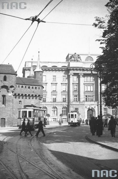Widok z ulicy Floriańskiej na Barbakan i budynek Narodowego Banku Polskiego przy ulicy Basztowej 20. Widoczne dwa tramwaje miejskie. 1930 rok