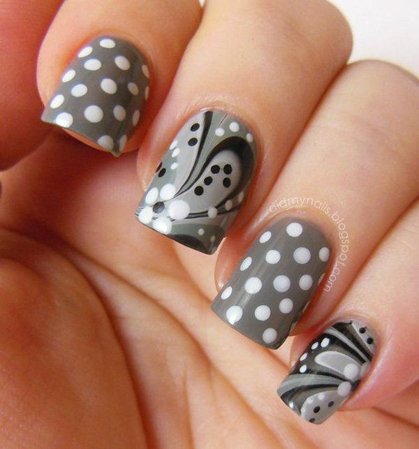 A very pretty flower patterned marble nail art design along with white polka dots and flower details on a copper polish base