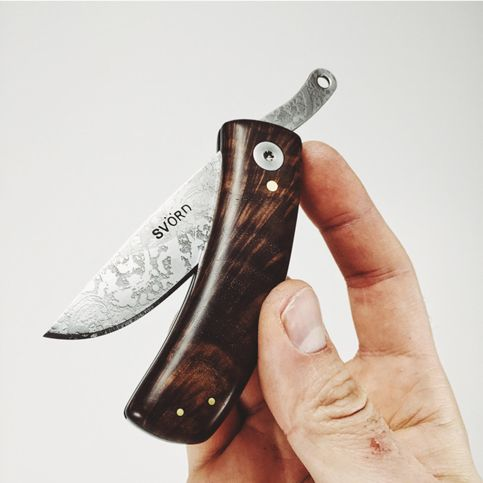 KUT Curly walnut - The KUT friction folding knife features a carbon steel Svörd blade made in New Zealand. Each blade is hand forged, and therefore a little different in appearance. Also features the signature WKRMN wood grain pattern applied directly into the steel. Handle is hand shaped from curly black walnut, black linen and white g10.