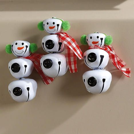 "Jingle Bell Snowmen Magnets With real buttons, jaunty fabric scarves, and pom-pom earmuffs, these snowmen magnets are made of wired-together, white-finished metal jingle bells. Each stands 2"" high with a strong magnet on the back"