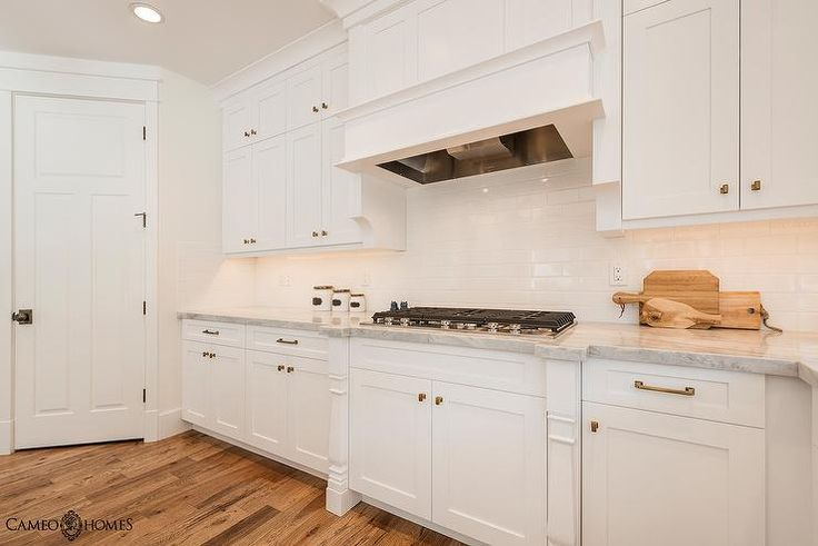 White on white kitchen features white shaker cabinets accented with antique brass hardware paired ...