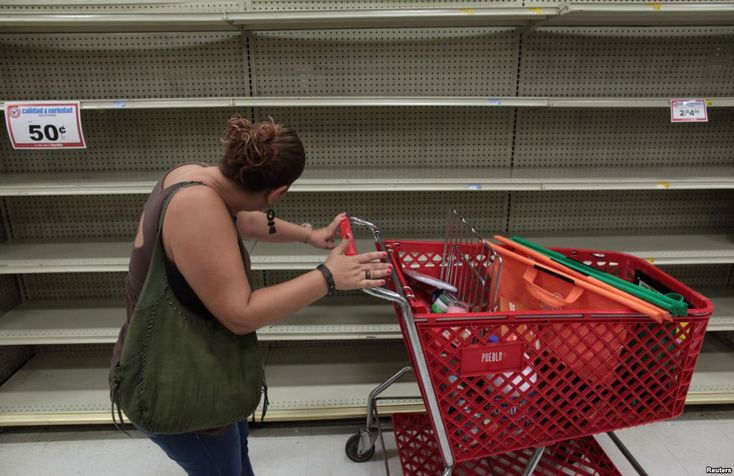 September 4, 2017:  A woman looks at empty shelves that are normally filled with bottles of water after Puerto Rico Governor Ricardo Rossello declared a state of emergency in preparation for Hurricane Irma, in San Juan, Sept. 4, 2017.