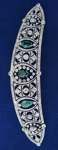 An Art Deco emerald and diamond bandeau, circa 1920. Designed as an open-work panel of geometric diamond lattice motifs, with three pear-shaped emeralds held within it, set in platinum.