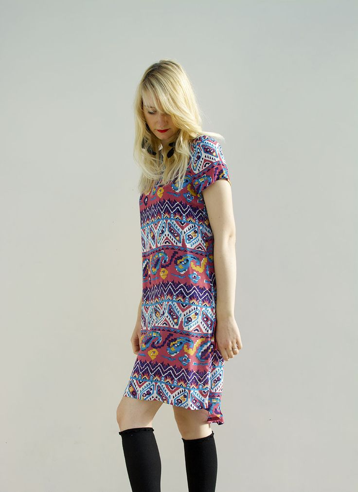 Aztec print tee style dress with cap sleeves and a dipped hem at the back. It has a comfy fit and would be perfect teamed with a longline kimono and knee high socks for daytime. Made to order in the UK. 100% Cotton.