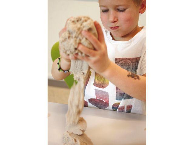 Kinderen klooien graag met zand, maar niet iedereen heeft de luxe van een zandbak in de tuin. Dit speciale zand is behandeld met een soort was, waardoor de korrels aan elkaar plakken. Het goedje is stevig genoeg om zandkastelen van te bouwen, maar als je er wat druk op uitoefent valt het weer uit elkaar. Het 'kinetische zand' droogt niet uit, geeft niet af en raakt niet verstrooid en is dus uitstekend geschikt om binnen te gebruiken.