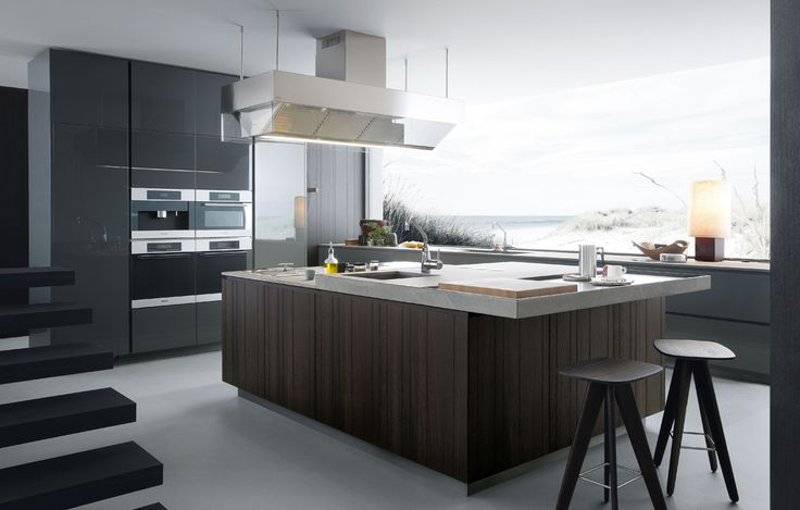 Kitchen Artex in the finishes ferro glossy lacquer and spessart oak with carved lines. Worktop in Fossena stone blaze with double thickness 20 mm and 80 mm . Island-hood Professional in stainless and transparent glass. Ice stools in spessart oak.