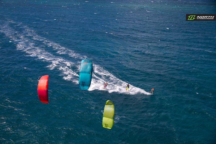 A trio of kitesurfers cruising on the 2015 North Rebel kites. North Kiteboarding and kitesurfing wallpaper.