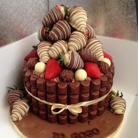 Another Red Velvet and Kinder Bueno Cake!!! Topped with Ferrero Rochers, Chocolate Dipped Strawberries, Lindt and oh so many Kinder Buneos held together with gold ribbon! #cake #chocolate #chocolatecake #kinderbueno #kinderbuenocake #ferrerorocher #lindt #lindor #strawberry #chocolatestrawberries #chocolateoverload #chocaholic #goldribbon #yum #overthetop #birthdaycake #cakesbyhassan #cakesinstyle #cakelife #cakeguide
