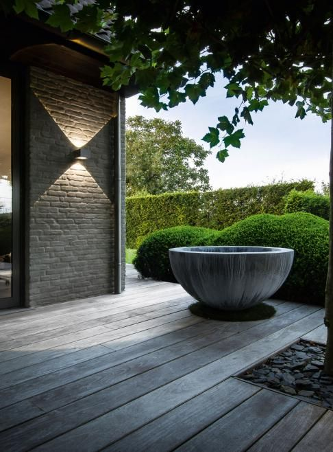 zinc bowl, wall sconce, shale top-dressing. love it against the green boxwoods. #garden #design