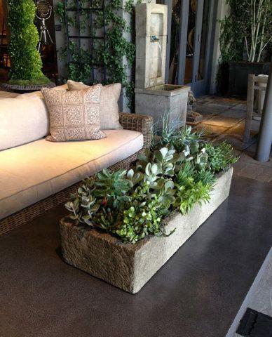 Incluídas na decoração desta área externa, as plantas ocupam um vaso de pedra e enfeitam a mesa de centro.