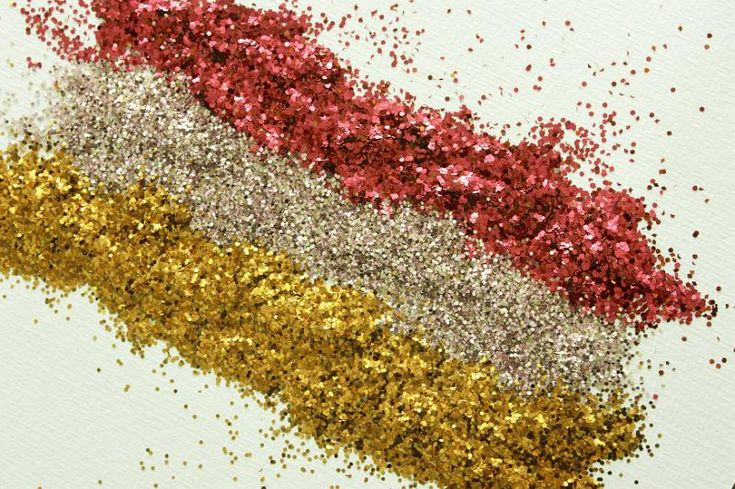 Gold and red glitter pattern with three lines of yellow and rose gold and red at a diagonal angle on a white background, high angle view for Christmas or festive occasions - free stock photo from www.freeimages.co.uk