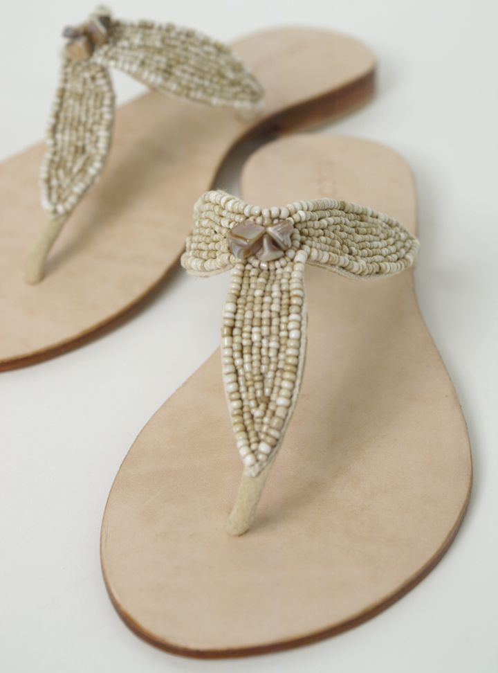 Breezy seaside beauties! Naturally chic and oh so comfortable. Sea shells and seed beads adorn these ivory warm-weather thongs with leather footbed and 1/2