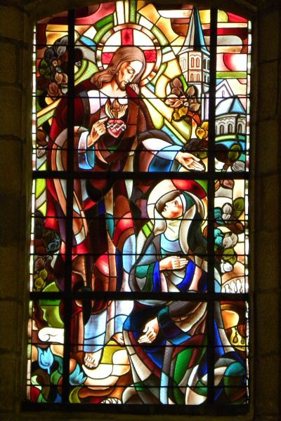 Marguerite-Marie Alacoque. - Heilig Hart verschijnt aan Marguerite-Marie. Op de achtergrond de kerk te Paray-le-Monial. ca 1930(?), glasschilderkunst. Frankrijk, Bretagne, Lesneven, St-Michel-Archange.