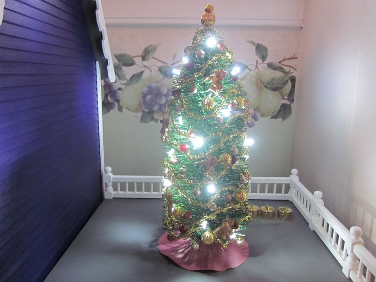 The fully lit tree.  Four strings of lights (10 lights per string) are glued in place into the tree with each string running to it's gold colored battery pack (sitting on the roof behind the tree).