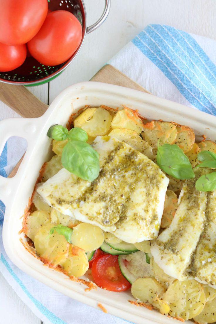 Ovenschotel met kabeljauw, courgette, tomaat en aardppelschijfjes. De vis wordt ingesmeerd met pesto.