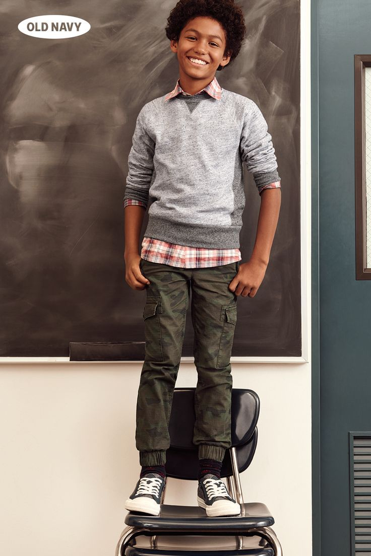 At the top of his class. Look smart in his back-to-school outfit: a plaid button-down shirt under a crew-neck sweater, finished off with boys jogger pants.