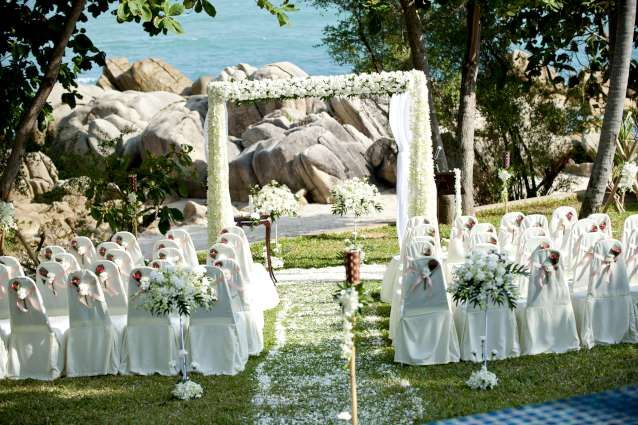 White roses, and orchids create this striking floral garden ceremony